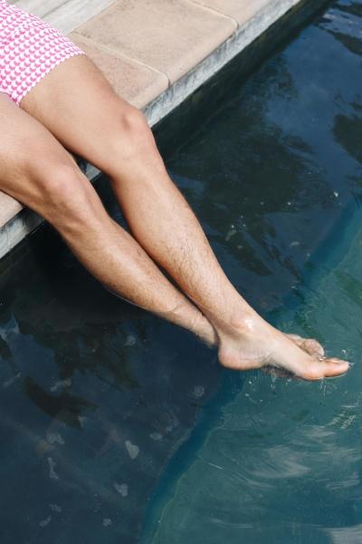 man dipping feet in swimming pool