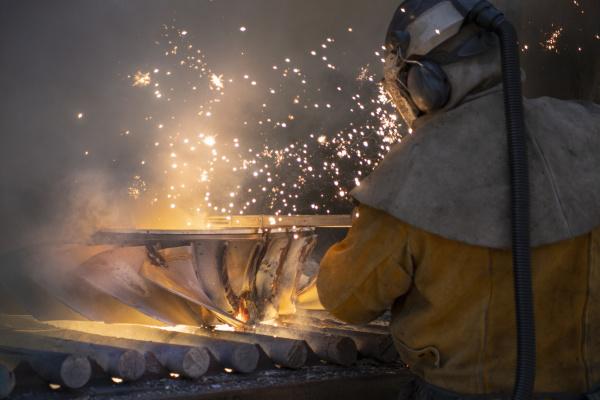 worker cutting up scrap titanium aircraft