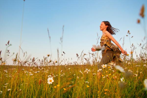 girl running through wildflower meadow