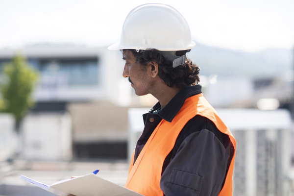 male engineer outside industrial building writing
