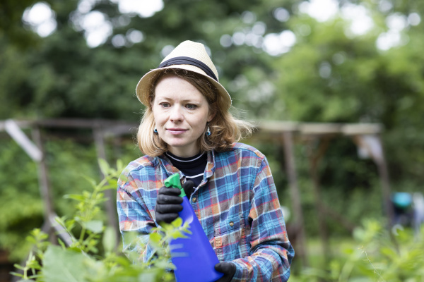 mid adult woman spraying plants in