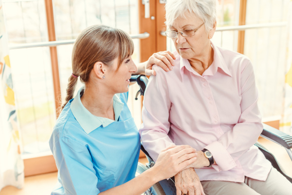 caregiver and senior woman in nursing