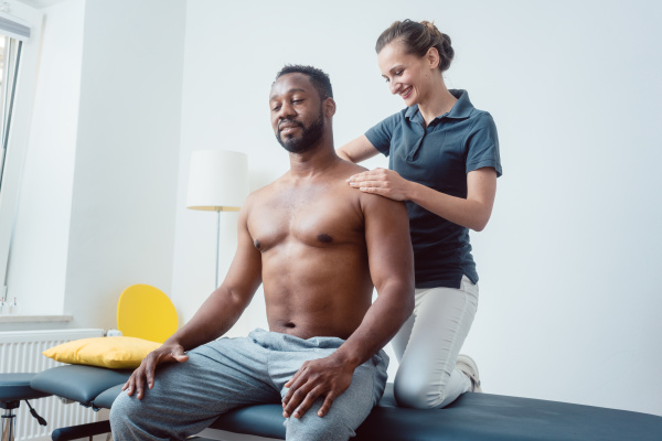 physical therapist massaging a young black