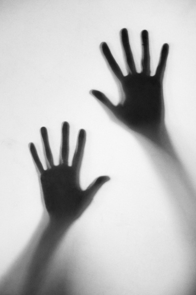 silhouette of womans hands touching frosted