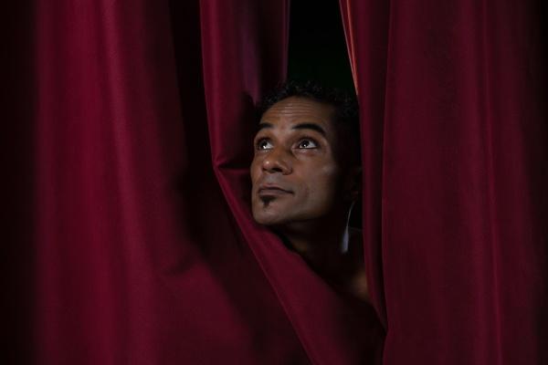 ballet dancer peeking through a stage