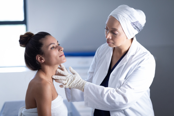 mature female doctor checking neck of