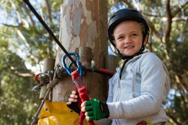 little girl wearing helmet standing near