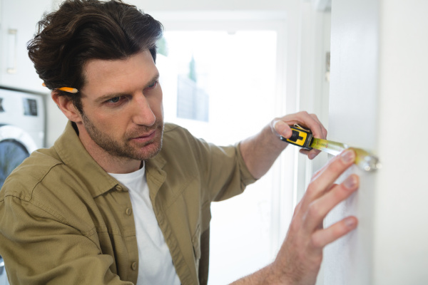 male carpenter measuring a wall