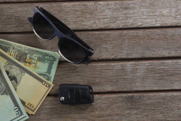 sunglasses and currency note on wooden