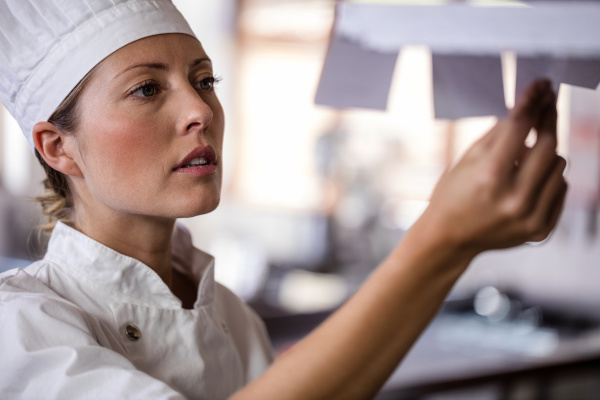 female chef looking at order list