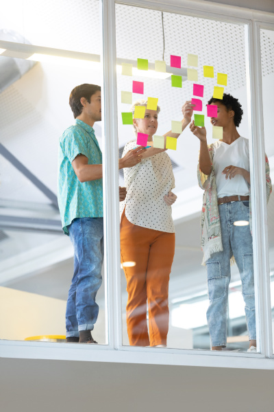 business people discussing over sticky notes