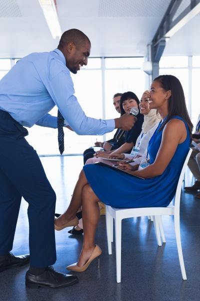 male speaker questioning businesswoman in business