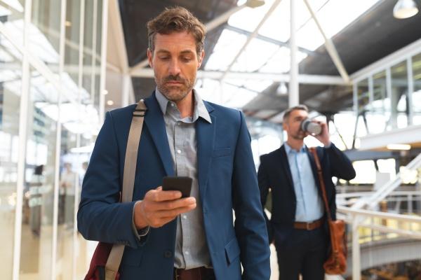 businessman using mobile phone while walking