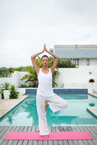 woman performing yoga near swimming pool