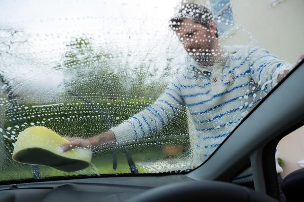 auto service staff washing a windscreen