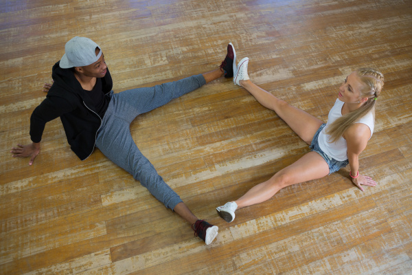 full length of dancers stretching legs