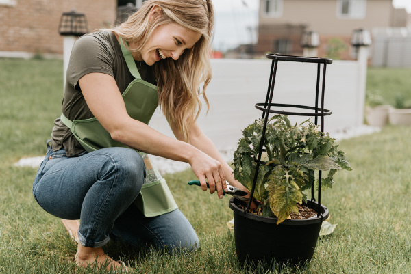 woman tending to potted plant in