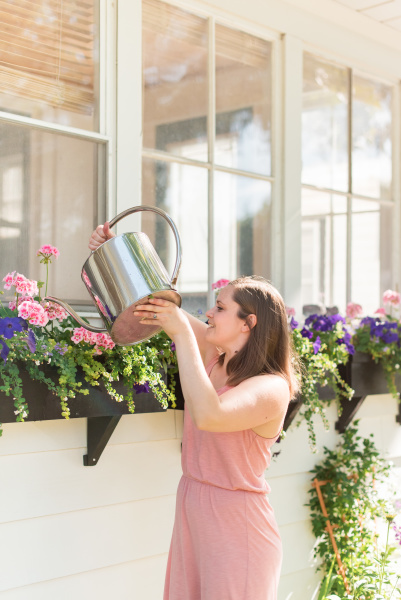 woman watering flowers in garden