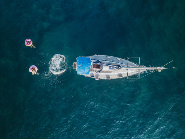 holiday makers swimming off sailboat on