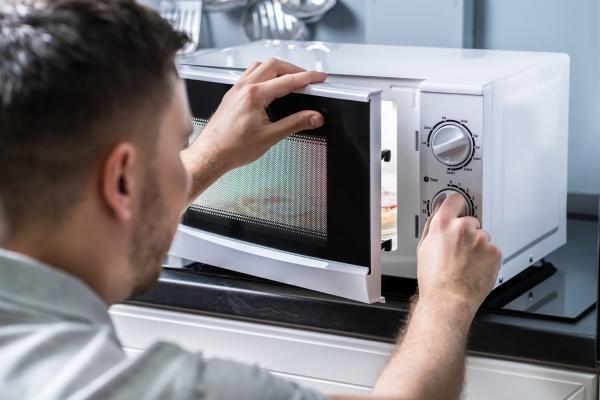 man preparing food in microwave oven