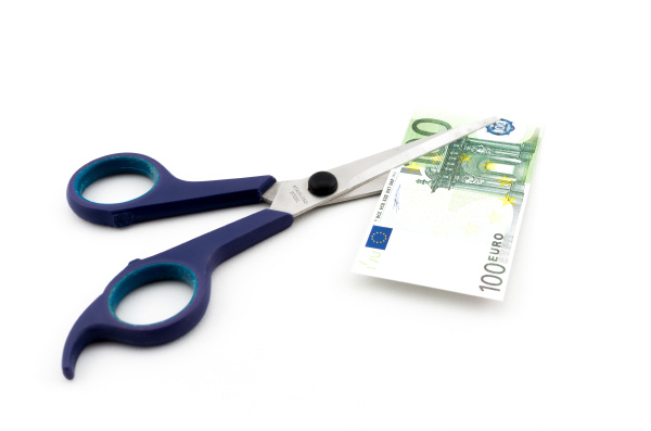 scissors cutting hundred euro banknote over