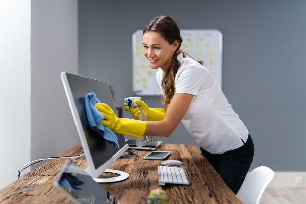 worker cleaning desk with rag