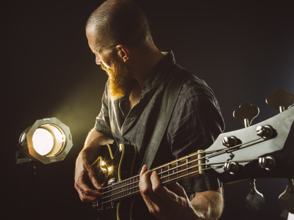 bearded man playing bass guitar with