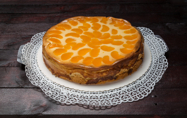 cream cake with tangerines on mahogany