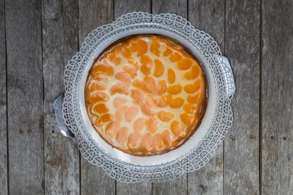 cream cake with tangerines on gray