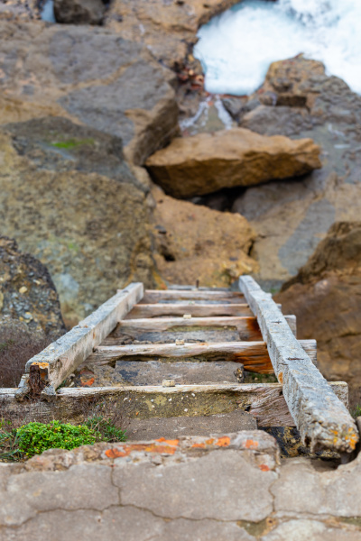 old wooden ladder on rock cliff