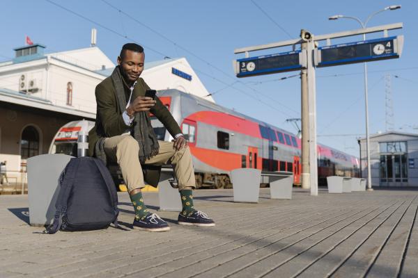 stylish man using smartphone while waiting