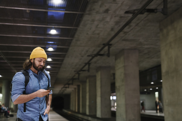 man waiting at platform using smartphone