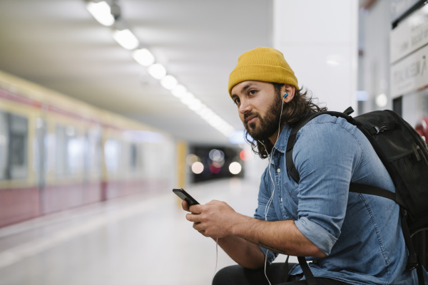man with backpack listening music with