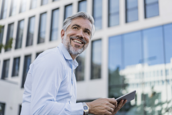 smiling mature businessman using tablet in