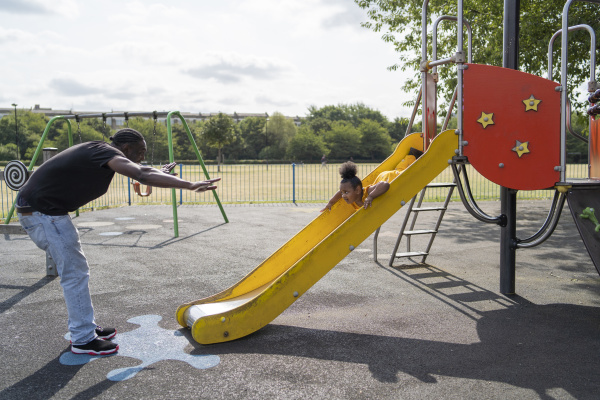 father with daughter sliding on a