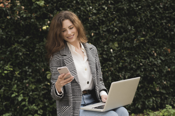 smiling woman using smartphone and laptop