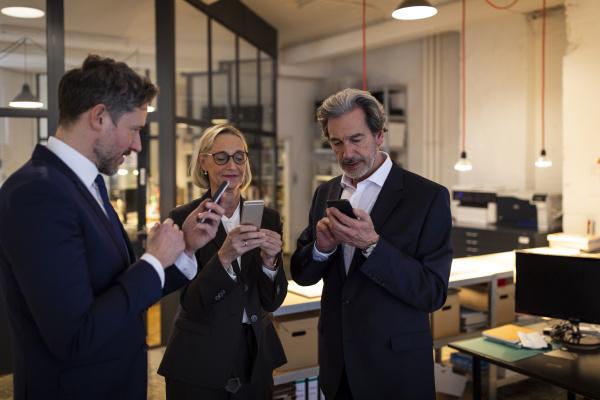 business people using smartphones in office