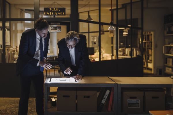 two businesssmen with shining tablet talking