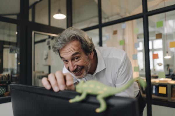 happy senior businessman with chameleon figurine