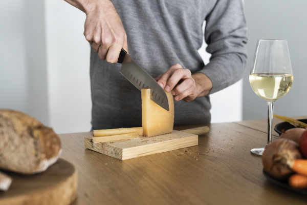 close up of man cutting cheese