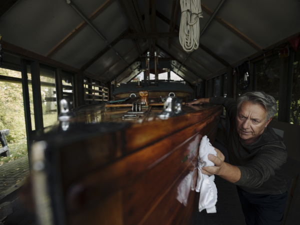 senior man cleaning wooden boat in