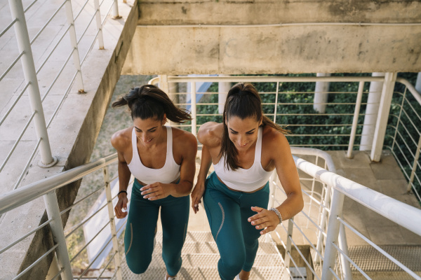 two sporty twin sisters running up