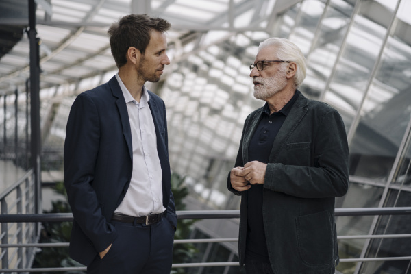 two businessmen talking in modern office