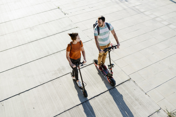 couple with backpacks riding electric scooters
