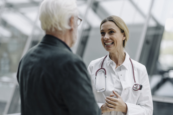 smiling female doctor talking to senior