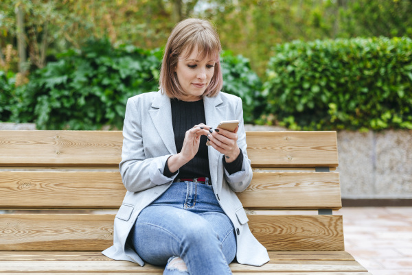 woman sitting on park bench using