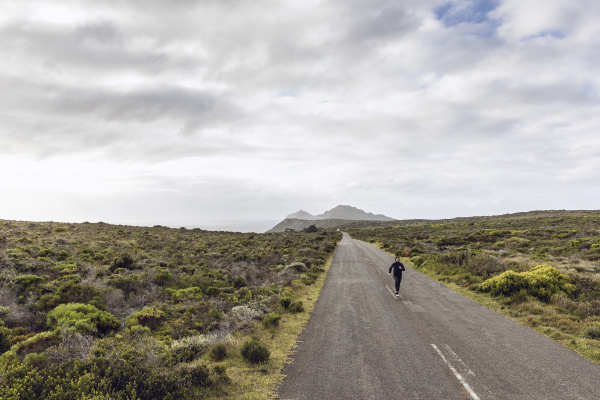 man jogging on country road cape