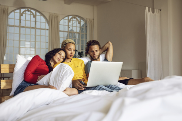 friends relaxing in bed at home