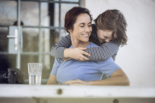 girl embracing mother sitting at home