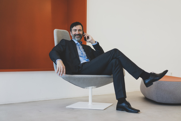 smiling mature businessman sitting in chair